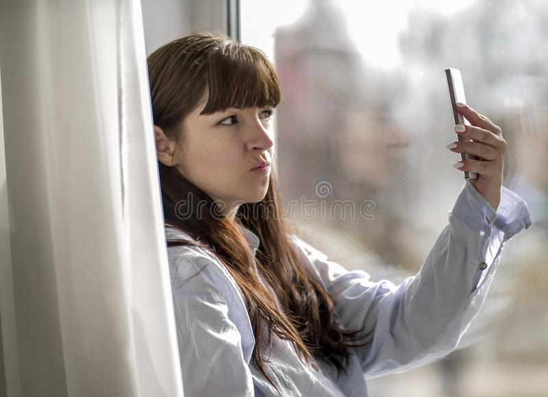 Young girl makes selfie while sitting by the window. Girl makes selfie while sitting by the window stock photo