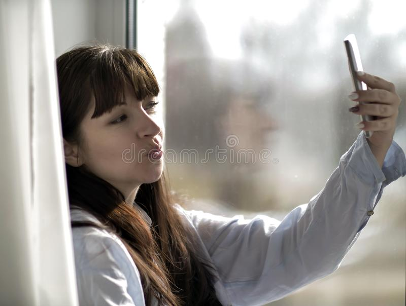 Girl makes selfie while sitting by the window. Young girl makes selfie while sitting by the window stock photo