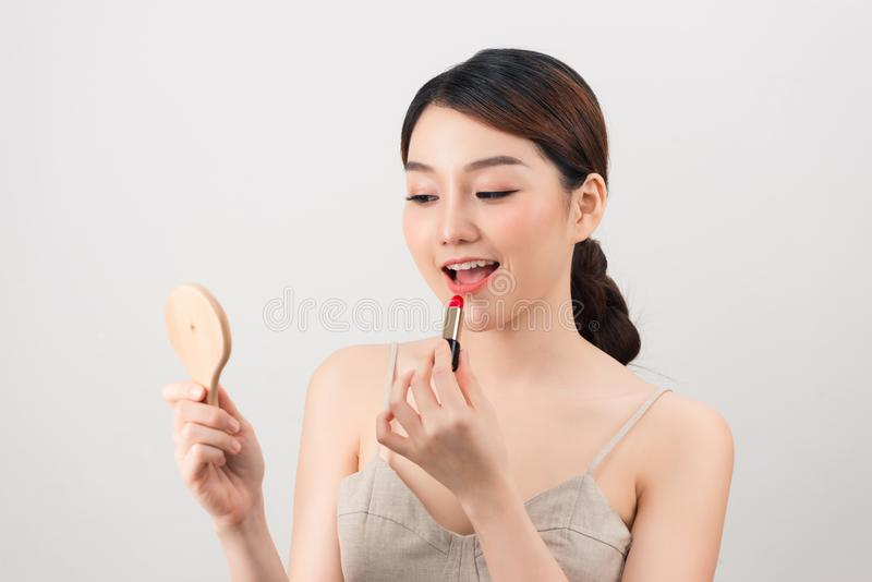 Girl makes up with lipstick and mirror royalty free stock photos