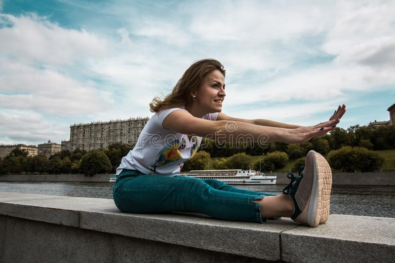 Girl makes warm up exercises before her fitness training or fit workout. Woman makes a warm-up, warms up before run. Against the background of the river and the stock photos