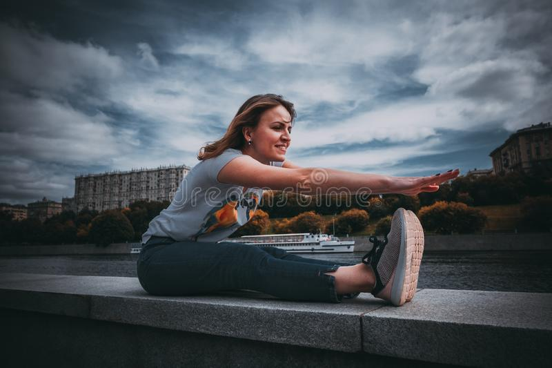 the girl makes a warm-up sitting on the waterfront. smiling woman stock photography