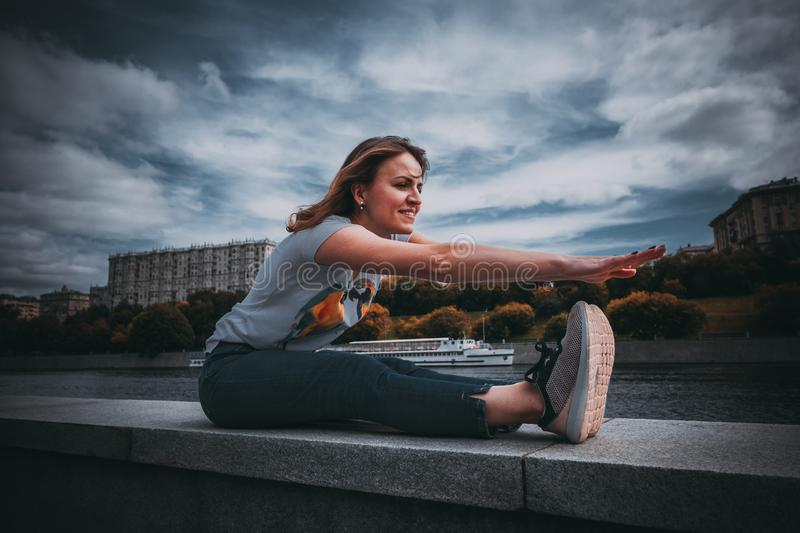 The girl makes a warm-up sitting on the waterfront. smiling woman. Beautiful woman wearing white t-shirt and a blue jeans makes warm up exercises. she sits on stock image
