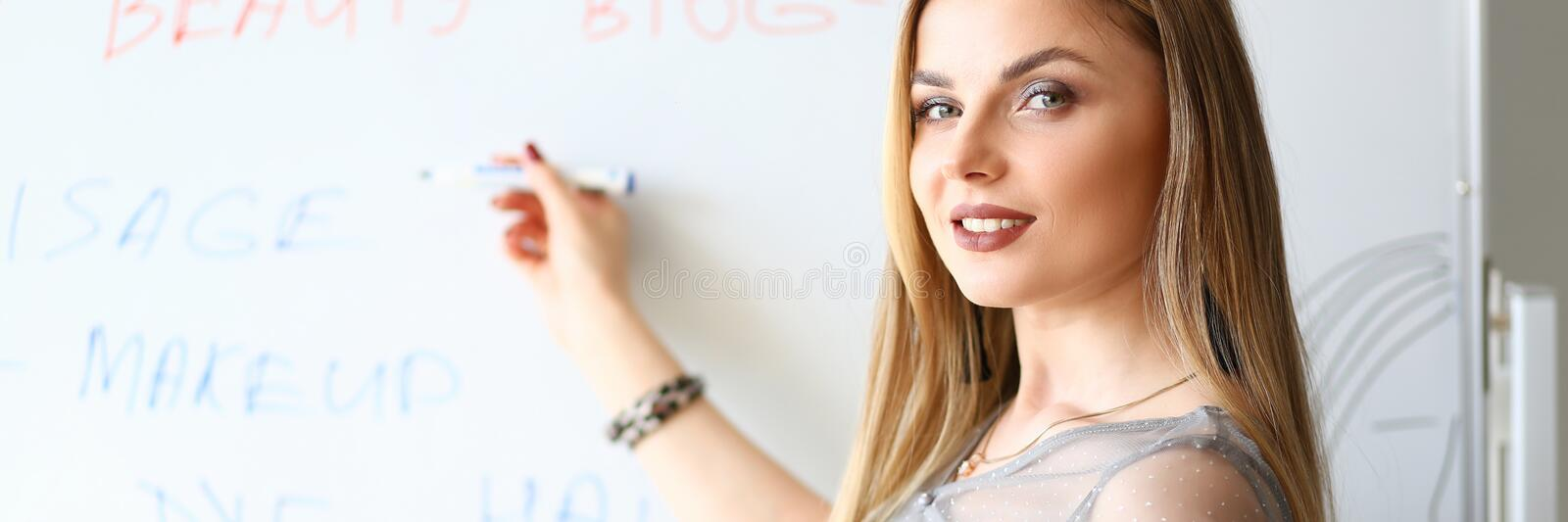 Girl Makeup Artist Beauty Product Presentation. Attractive Blond Woman Writing Tutorial Points on Board. Woman Planning Lecture. Smiling Businesswoman Holding stock photo