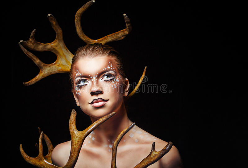 Girl with makeup deer. Young attractive cute girl with an unusual make-up of wild deer stock photo