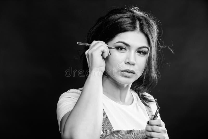 Girl makeup face hold tweezer for eyelash extension. Beauty shop concept. Professional eyelash extension tweezer. Makeup stock photo