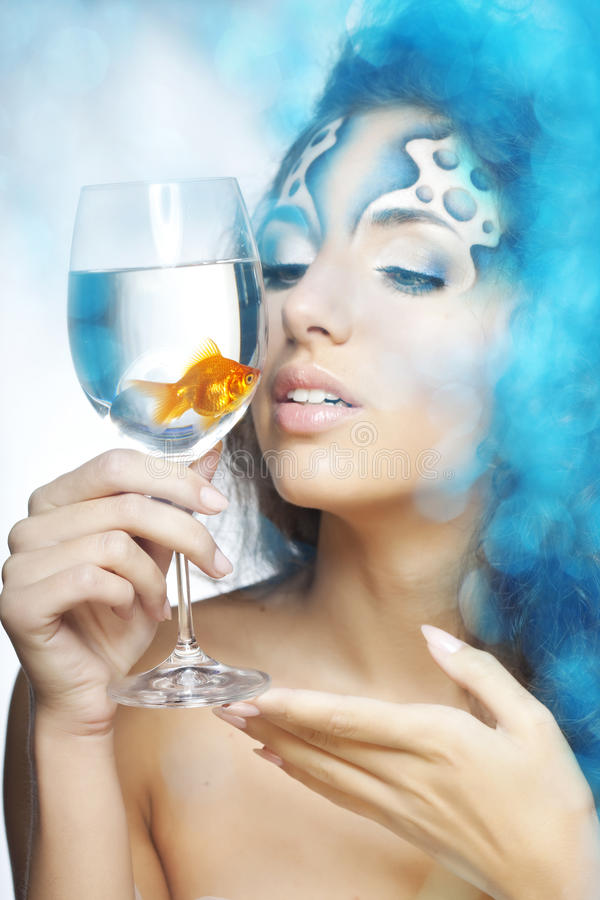 Girl with makeup, with a fish in a glass. The image of a girl with makeup with a fish in a glass in her hand royalty free stock image