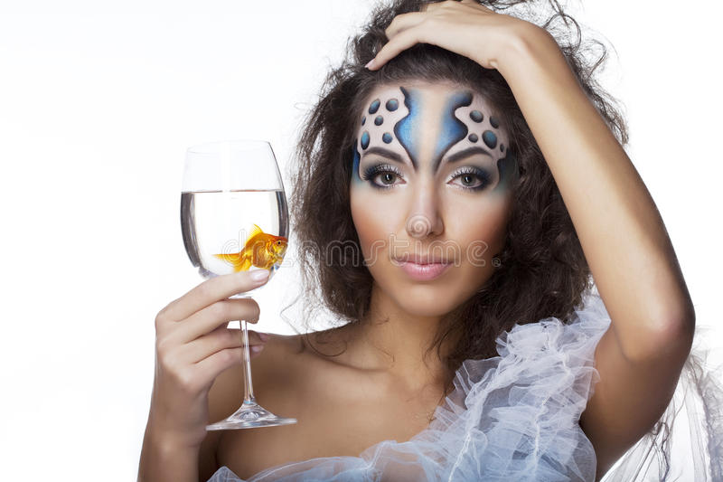 Girl with makeup, with a fish in a glass. The image of a girl with makeup with a fish in a glass in her hand stock image