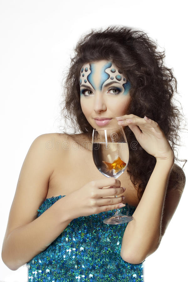 Girl with makeup, with a fish in a glass. The image of a girl with makeup with a fish in a glass in her hand royalty free stock photography