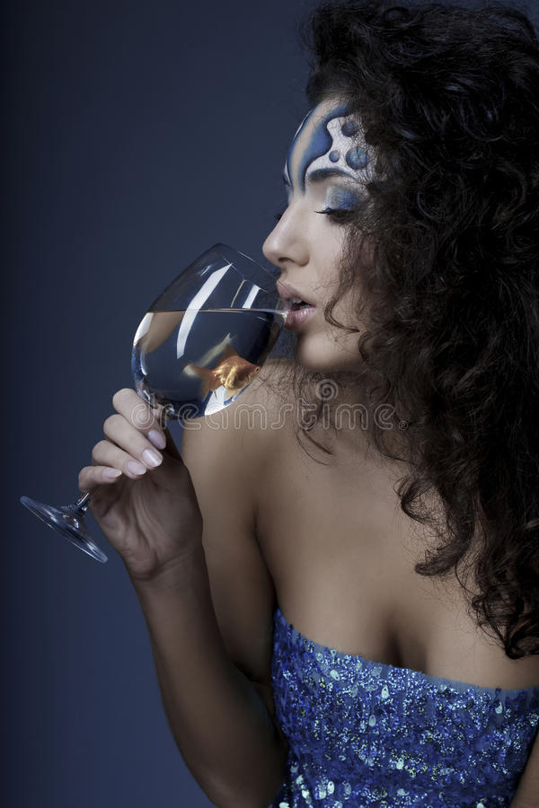 Girl with makeup, with a fish in a glass. The image of a girl with makeup with a fish in a glass in her hand royalty free stock photo