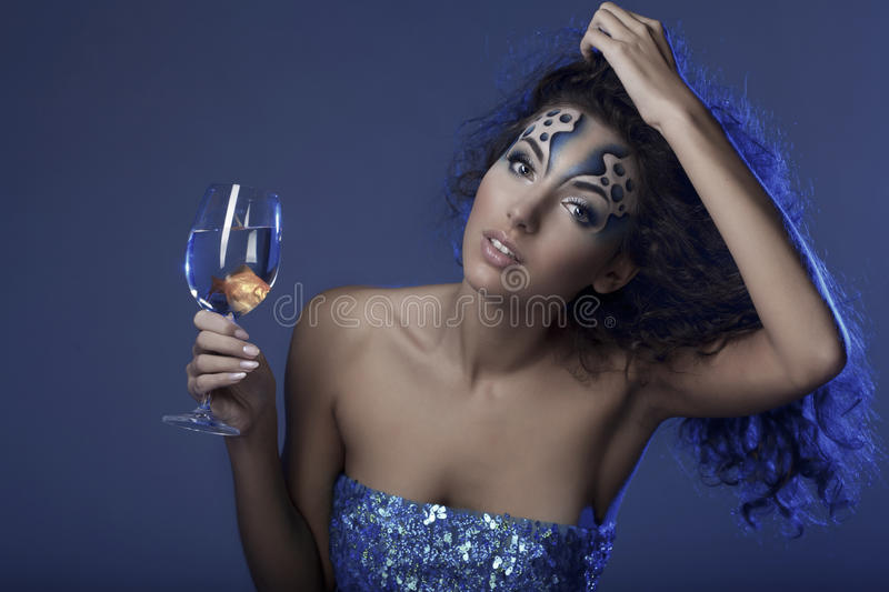 Girl with makeup, with a fish in a glass. The image of a girl with makeup with a fish in a glass in her hand stock photos