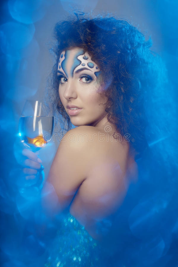 Girl with makeup, with a fish in a glass. The image of a girl with makeup with a fish in a glass in her hand royalty free stock photos