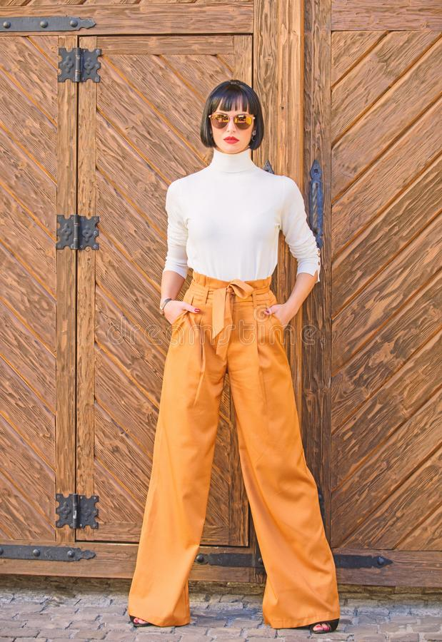 Girl with makeup posing in fashionable clothes. Fashionable outfit slim tall lady. Fashion and style concept. Woman walk. In loose pants. Woman fashionable royalty free stock photography