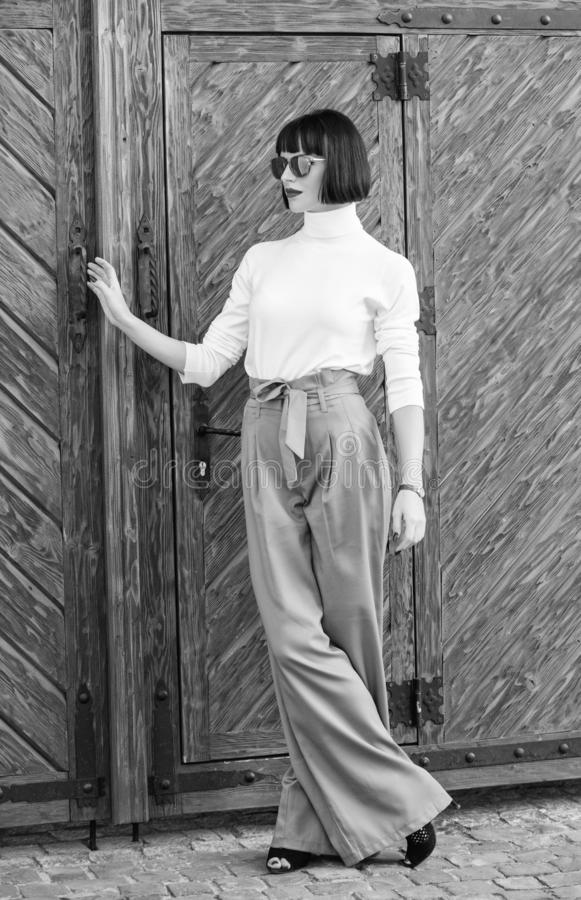 Girl with makeup posing in fashionable clothes. Fashionable outfit slim tall lady. Woman walk in loose pants. Woman. Fashionable brunette stand outdoors wooden royalty free stock photos