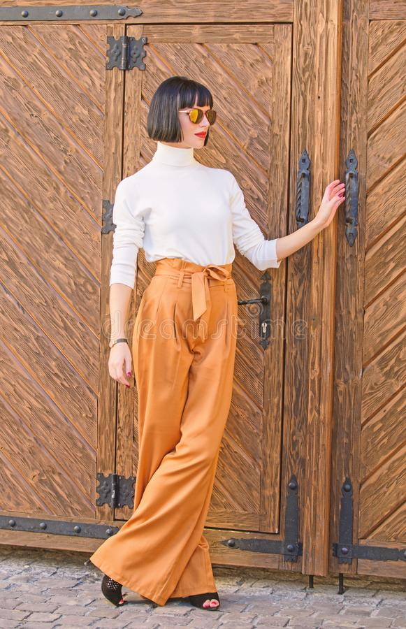 Girl with makeup posing in fashionable clothes. Fashionable outfit slim tall lady. Woman walk in loose pants. Woman. Fashionable brunette stand outdoors wooden royalty free stock image