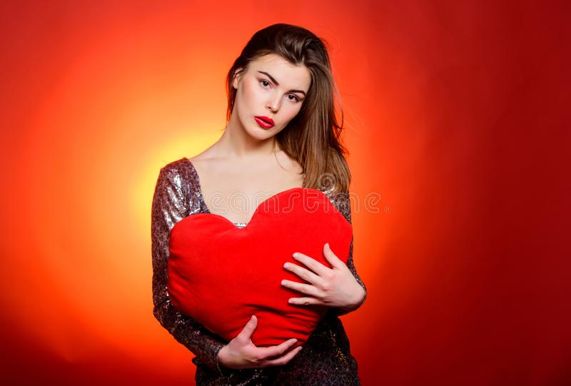 Girl makeup and decollete dress. Woman attractive fashion model hold heart toy valentines decoration. Love and royalty free stock photo