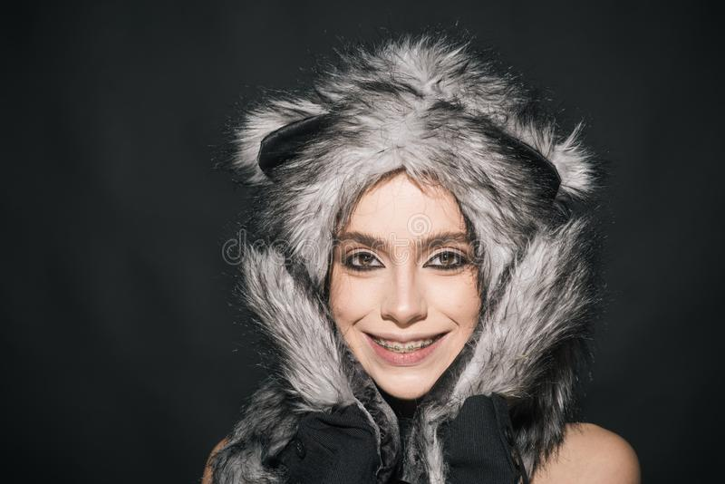 Girl with makeup wears fluffy fur hat with ears like cat. Cute kitty outfit. Carnival and Halloween ideas. Cute outfit stock image