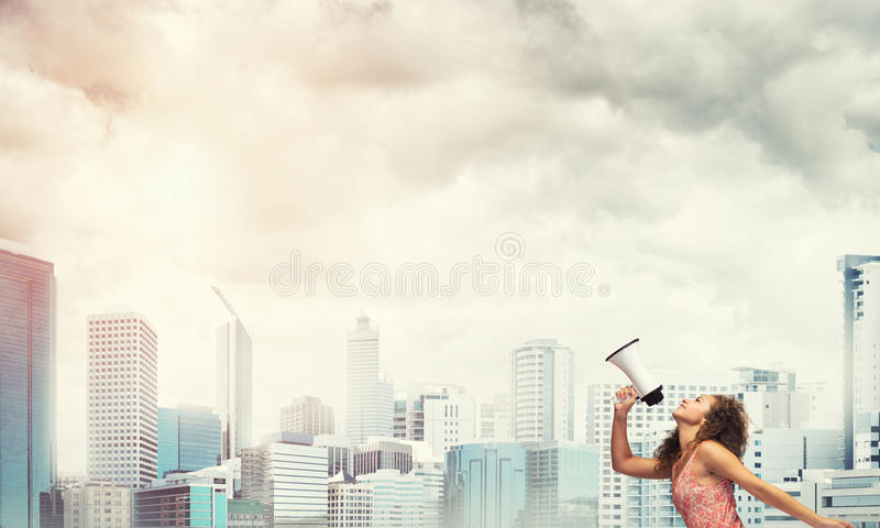 Girl making announcement. Young woman against city background screaming emotional in megaphone stock image