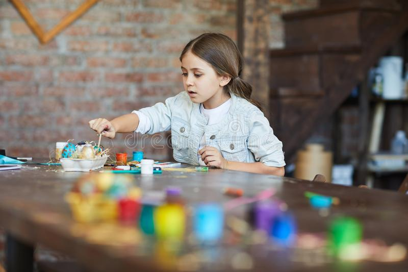 Girl Making Easter Decorations. Portrait ofcute little girl making Easter decorations in arty studio, copy space royalty free stock photo