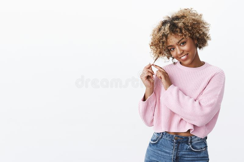 Girl making flirty gazed at camera rolling curl on fingers silly and coquettish looking romantic and tender smiling royalty free stock images