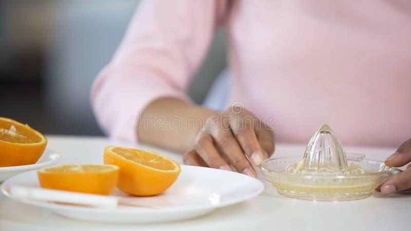 Girl making fresh orange juice, handheld juicer and fruits on table, energy. Stock photo stock photo
