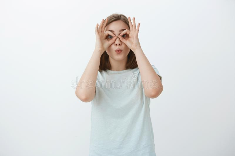 Girl making funny faces wasting time. Portrait of playful and joyful immature cute woman in t-shirt making circles over. Eyes with hands as if looking through royalty free stock photo