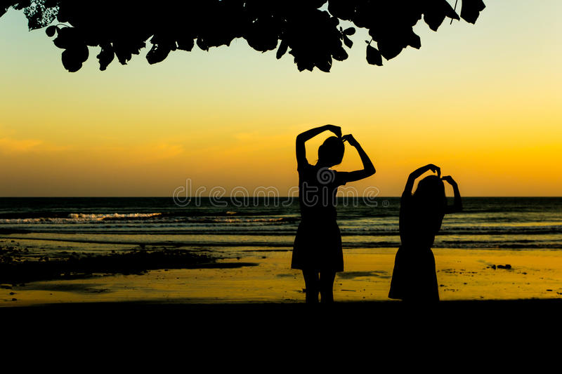 Girl making heart shape at sunset beach. royalty free stock photography