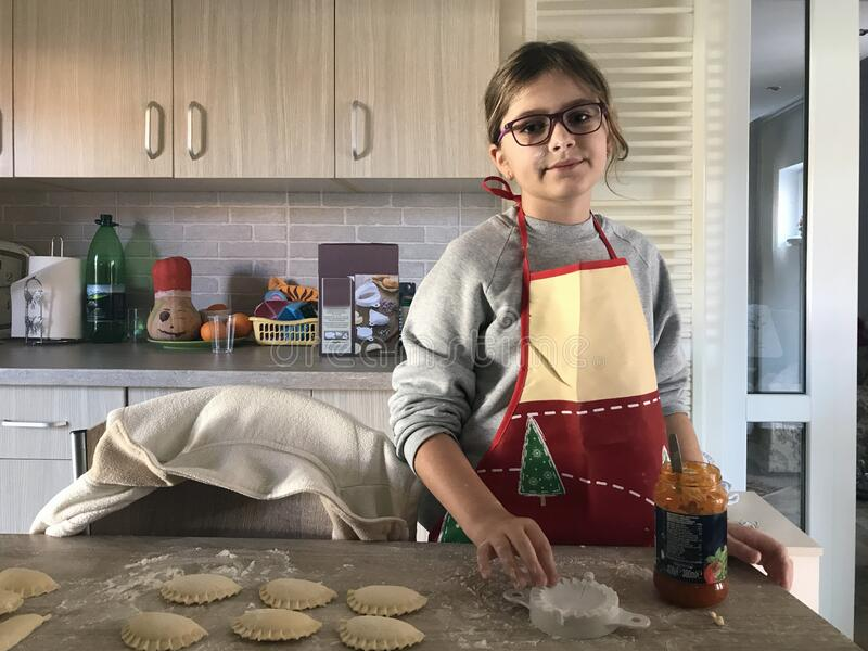 Girl making jam filled shells. A young girl with glasses and an apron making jam filled shells at home stock image