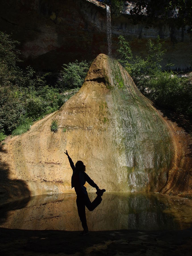 A girl making meditation. Exercice in natural place with a river falling on a big white and yellow rock - The Pain de Sucre - France - The Alps stock photography