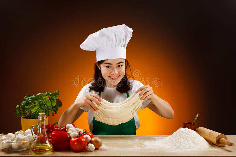 Girl making pizza dough. Girl making dough. Food ingredients on table stock image