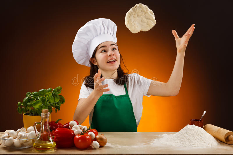 Girl making pizza dough. Girl making dough. Food ingredients on table stock images