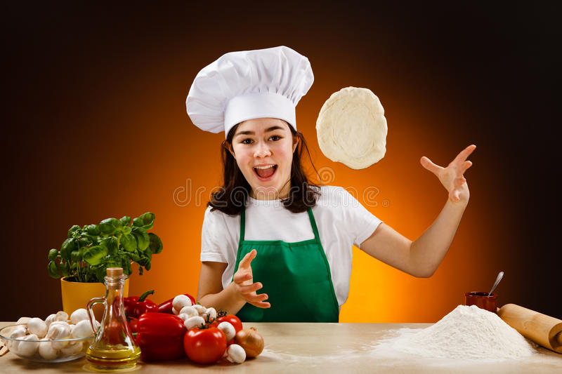 Girl making pizza dough. Girl making dough. Food ingredients on table royalty free stock photo