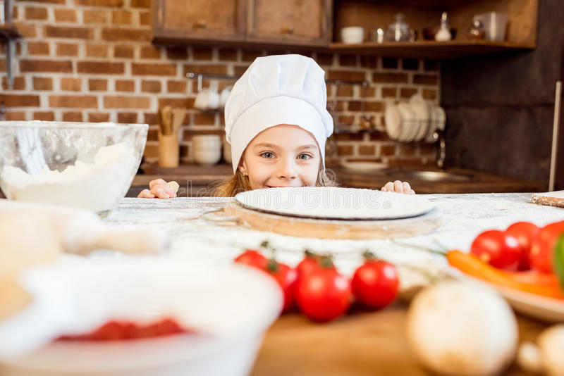 Girl making pizza dough with pizza ingredients in kitchen royalty free stock images