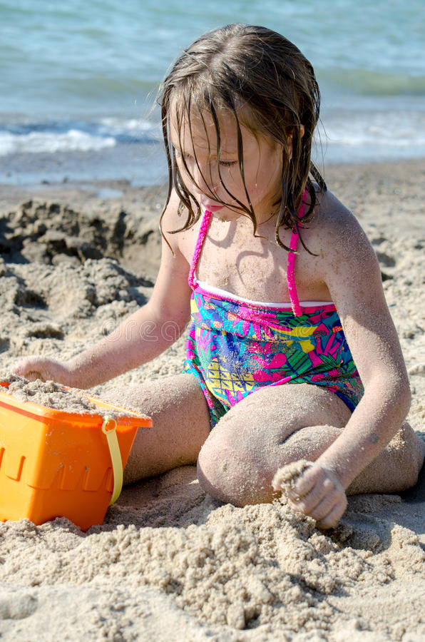 Girl making sand castles on beach royalty free stock image