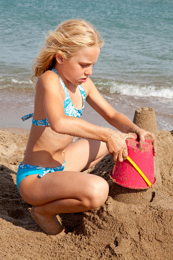 Girl is making sandcastle on the beach stock photo