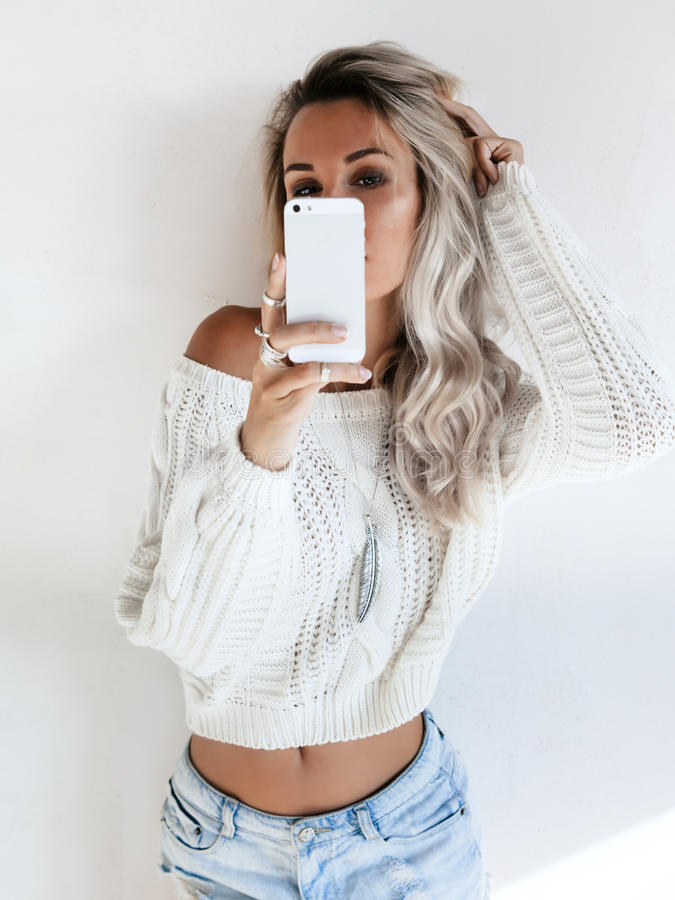 Girl making selfie. Blond girl wearing white sweater and jeans shorts making selfie by her smartphone in the mirror. Blogger taking photo of self fashion look royalty free stock photo