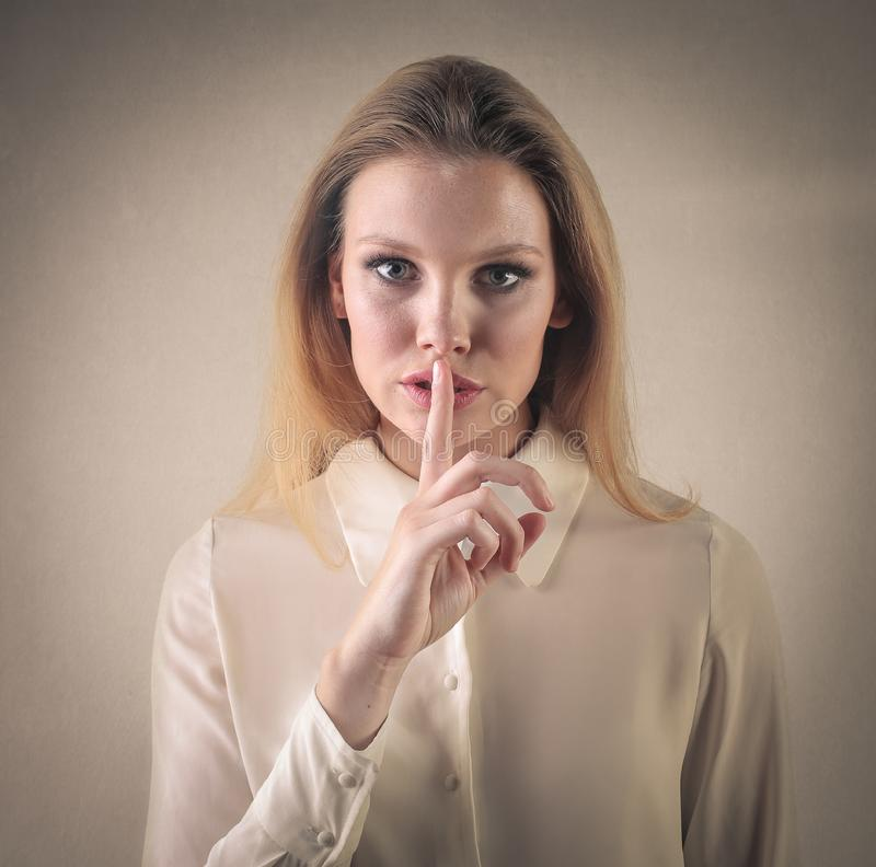 Girl making the silence gesture royalty free stock images