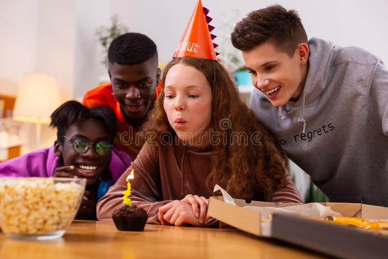 Girl making a wish sitting near little birthday muffin with candle stock photo