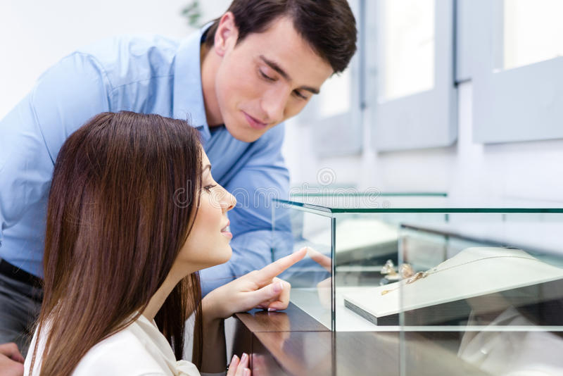 Girl with male chooses expensive jewelry stock image