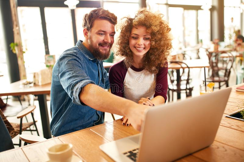 Girl with male looking at laptop. Curly girl with male looking something at laptop stock images