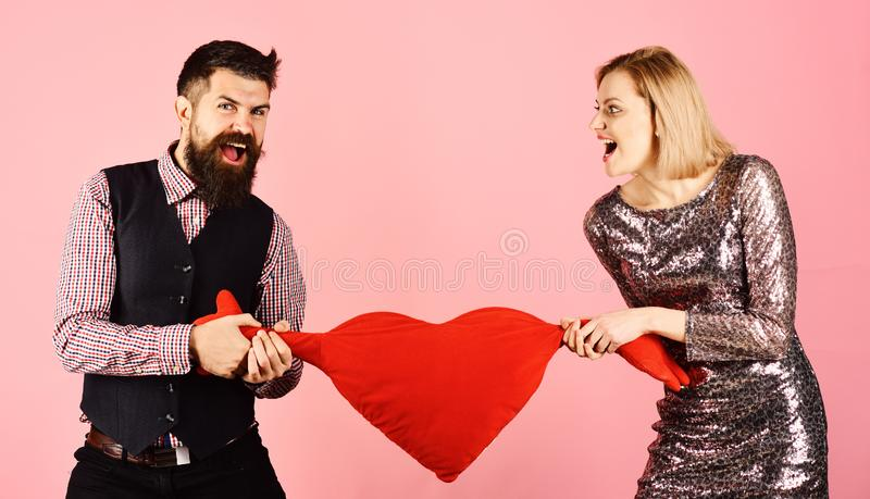 Girl and man with angry faces play with toy heart stock photo
