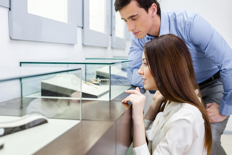 Girl with man chooses expensive jewelry royalty free stock images