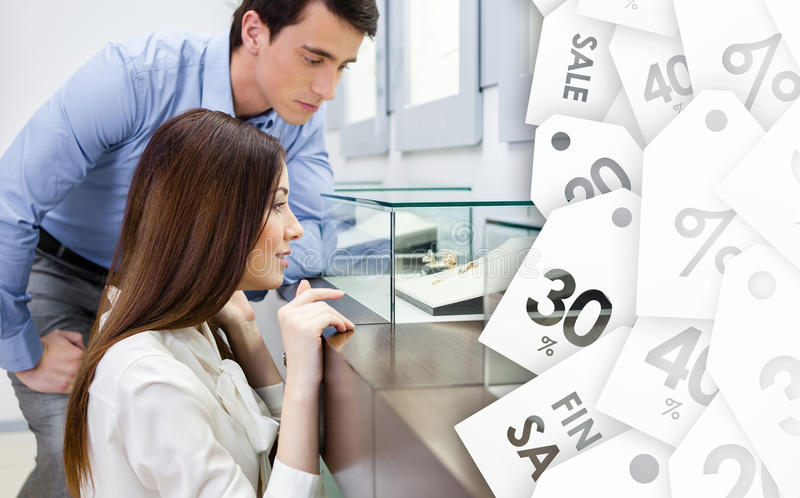 Girl with man chooses expensive jewelry on sale stock image