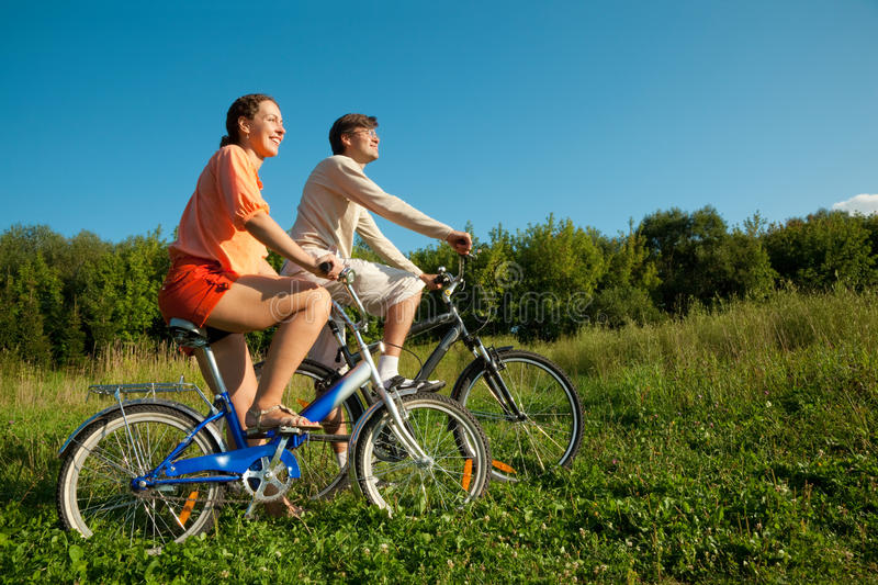 Girl and man go for drive on bicycles in sunny day stock photography