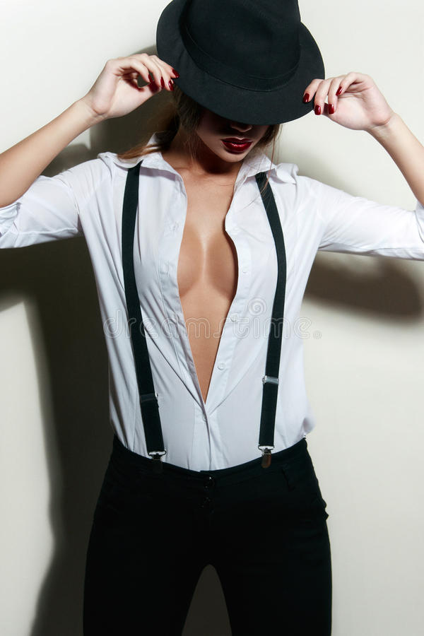 The girl in a man's shirt with suspenders . Black fedora stock image