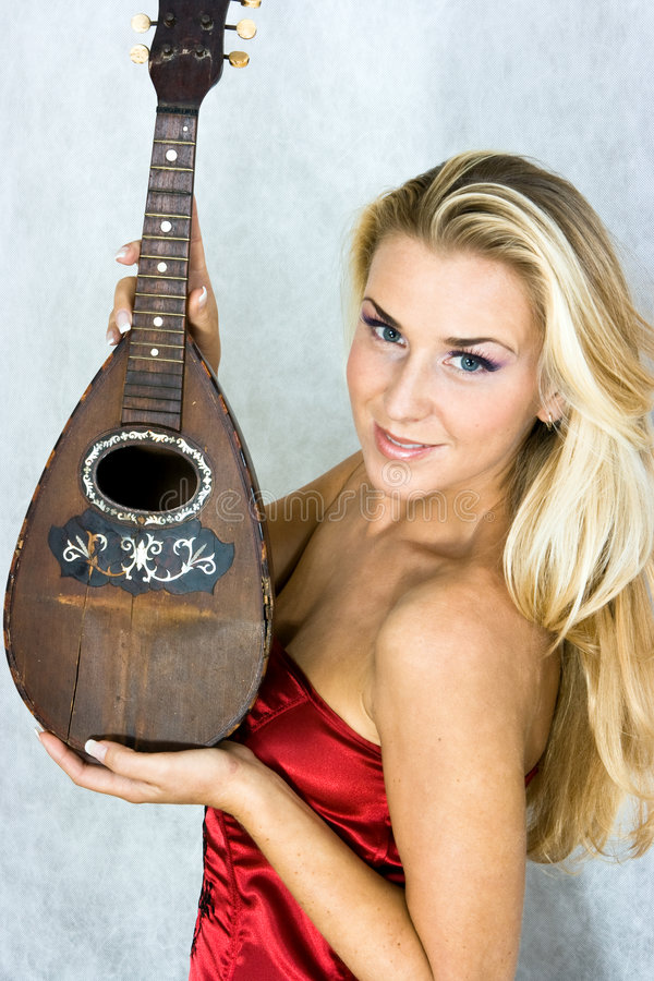 Girl with mandolin. Girl in red corset with old mandolin in hands stock photography