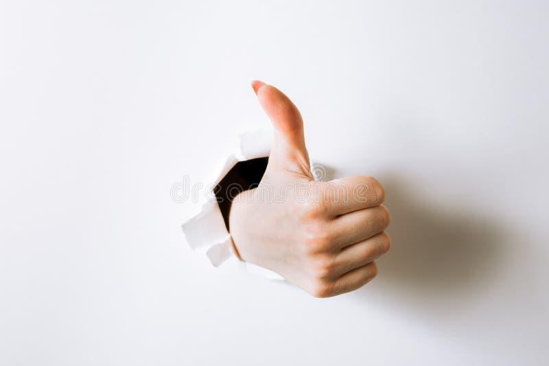 girl& x27; mano de s que perfora con el papel y las demostraciones el A.C. del gesto imagen de archivo libre de regalías