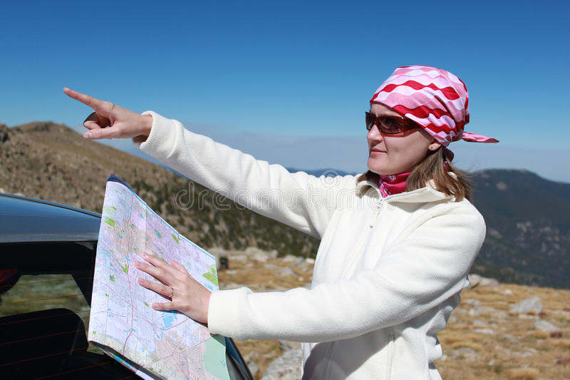Girl with map trying to locate the route royalty free stock photos