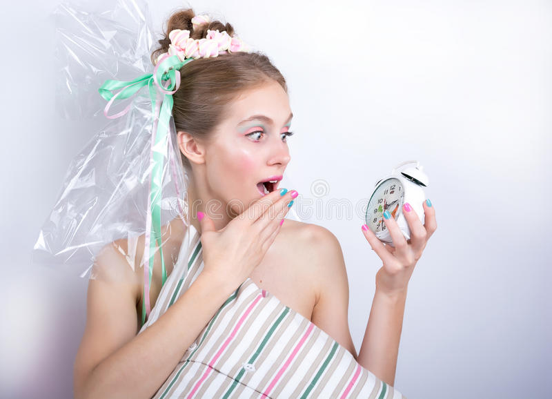 Girl-marshmallow with a pillow and alarm clock in her hands afraid of being late. royalty free stock image