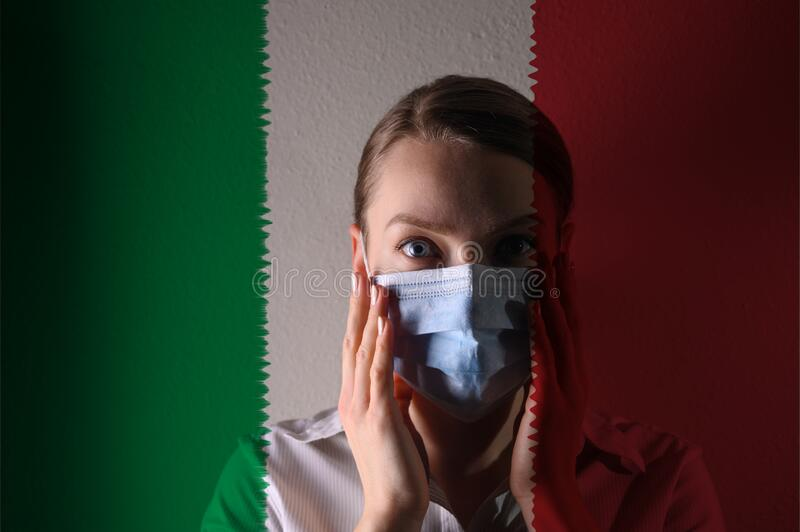Girl in a mask against the background of the Italy flag, coronavirus, danger and threat, outbreak of a dangerous virus. Photo for. Articles, news royalty free stock photos