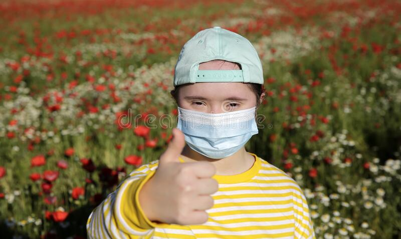 Girl with mask on the face on background on the flowers field stock photos